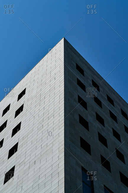 Exterior of contemporary building with tiled walls and many windows located against cloudless blue sky in city