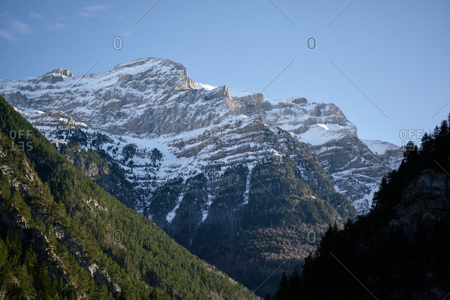 Rocky slopes of mountain chain with snowy peaks in daylight