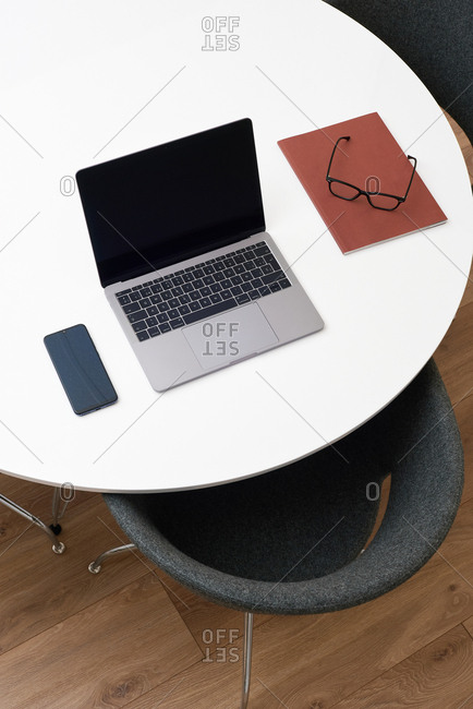 Above view of white table with laptop, mobile phone, and eyeglasses in office