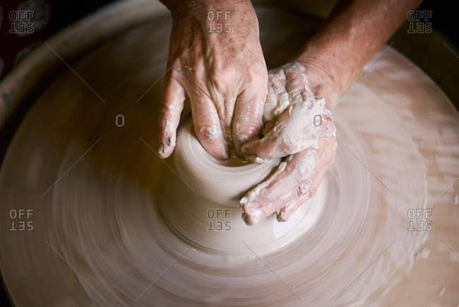 Hands of unrecognizable person forming clay pot on turning pottery wheel in studio