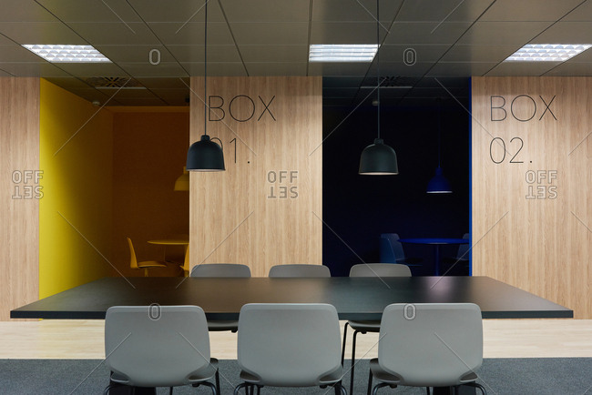 Black table with gray chairs located near empty colorful boxes in modern office