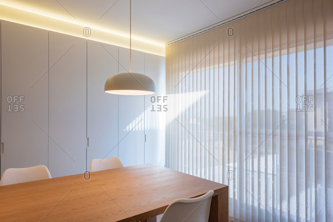 Table with chairs located under lamp near window in simple light conference room in modern office