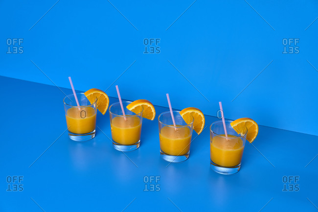 Composition of glasses with orange juice on blue background