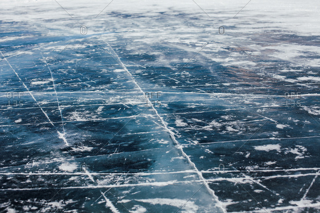 Abstract view of cracks on the ice of a frozen lake in winter