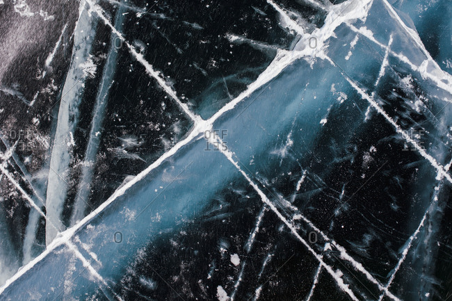 Abstract view of cracks on the ice of a frozen lake in winter close up