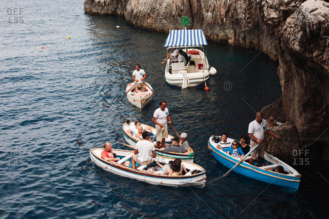 Capri, Italy - July 25, 2012: Tourists in boats prepare to enter the Blue Grotto