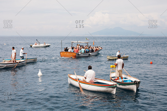 Capri, Italy - July 25, 2012: Tourists in boats outside of the Blue Grotto