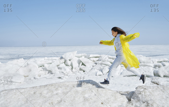 Young adult woman running on ice