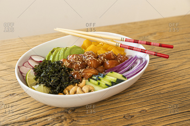 Salmon poke bowl on an old wooden table with chopsticks