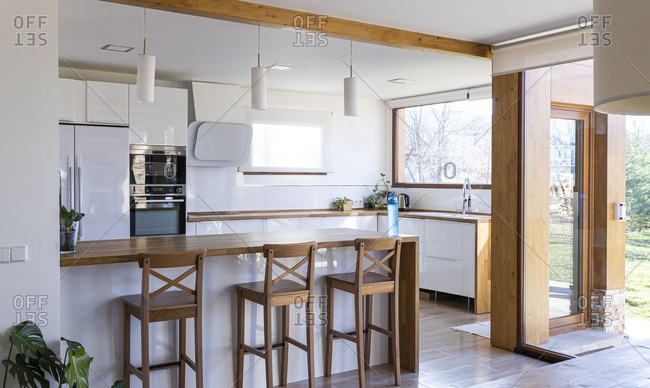 Stylish kitchen with white walls, wooden countertops and bar, and plants