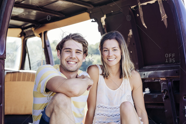 Portrait of smiling young couple on vacation relaxing in van