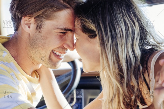 Closeup of smiling romantic couple with face to face in van during road trip