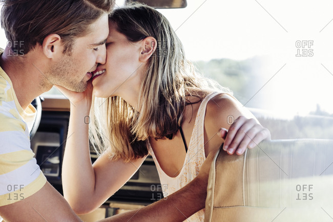 Young affectionate boyfriend and girlfriend kissing in van during road trip