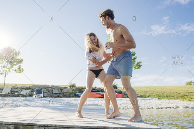 Full length of playful young couple enjoying on jetty against sky during summer vacation