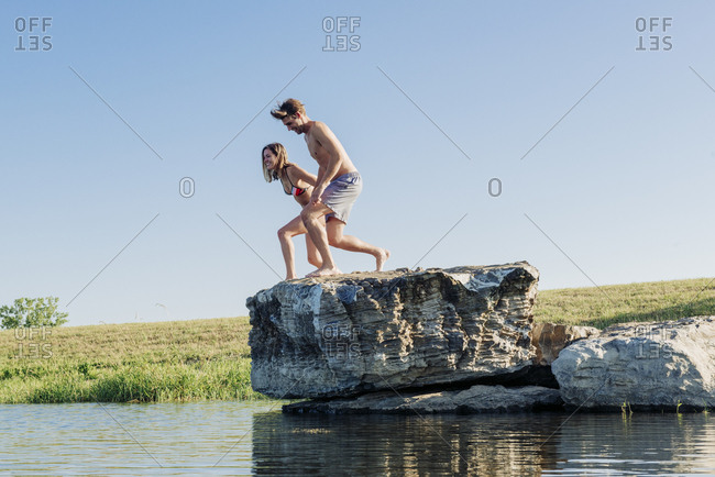 Full length of young carefree couple about to jump from rock in lake against sky