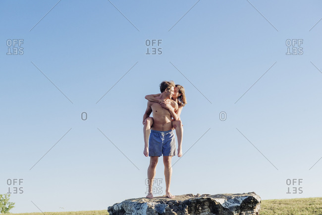 Full length of young shirtless man giving piggyback to girlfriend while standing on rock against blue sky