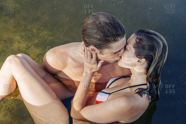 High angle view of young boyfriend and girlfriend kissing in lake on sunny day