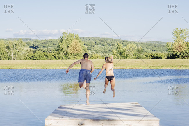 Rear view of carefree couple holding hands while jumping in lake from jetty during sunny day