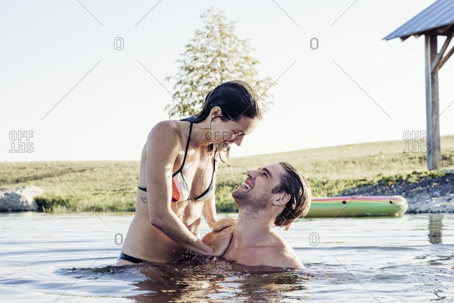 Carefree young couple enjoying a swim in lake against sky on sunny day