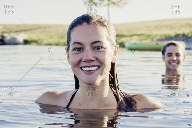 Portrait of smiling beautiful young woman swimming in lake with boyfriend on sunny day