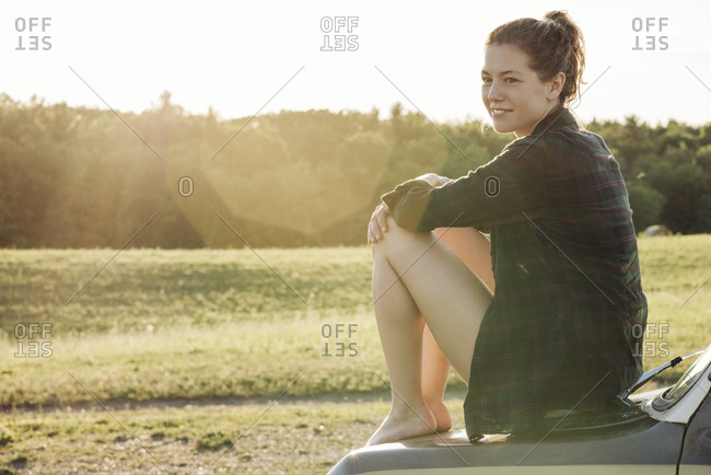 Full length side view of smiling young woman sitting on van hood during sunny day