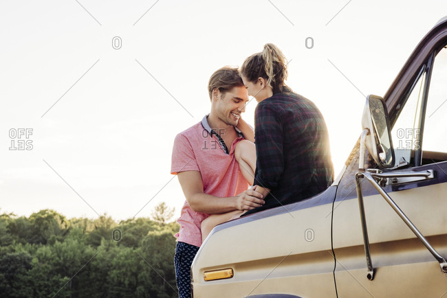 Smiling young couple spending leisure time while woman sitting on van hood against sky during sunny day