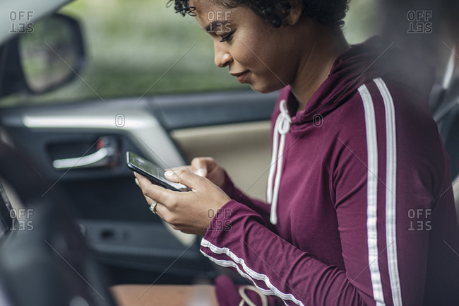 Woman Texting On Mobile Phone In Car