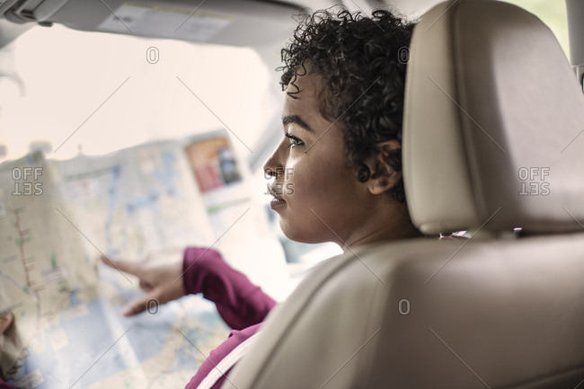 Young Woman Looking Away While Pointing At Map In Car