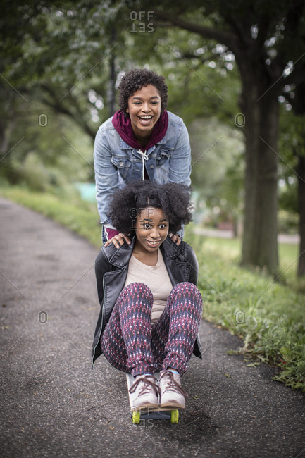 Cheerful Woman Pushing Female Friend On Skateboard At Park
