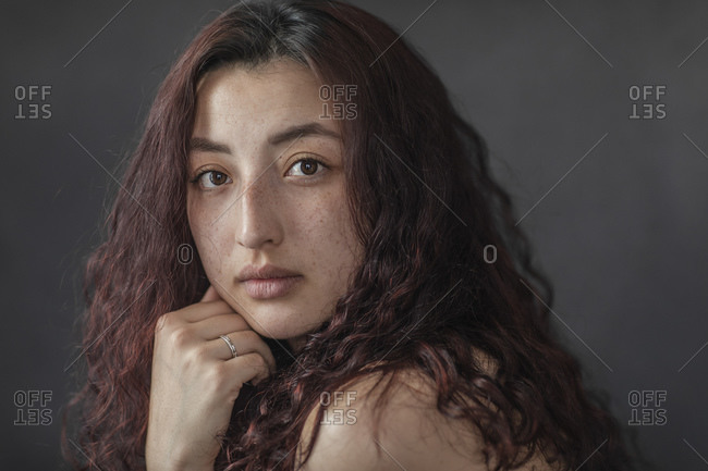 Closeup portrait of young gorgeous brunette woman sitting with hand on chin against black background