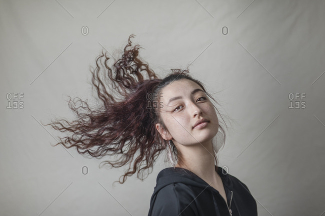 Closeup portrait of young brunette woman tossing her long curly hair against backdrop in studio