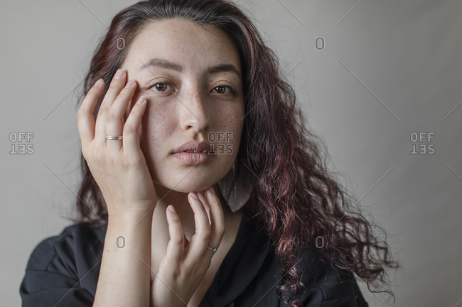 Closeup portrait of gorgeous young woman touching her face against backdrop in studio