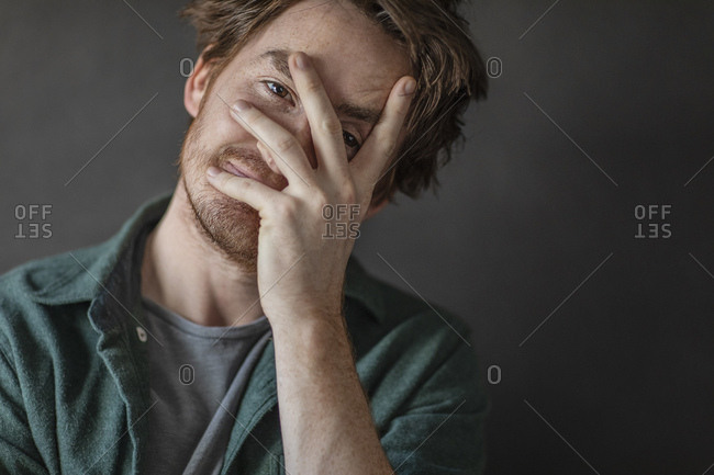 Closeup of attractive man covering face with hand while peeking through fingers against black background