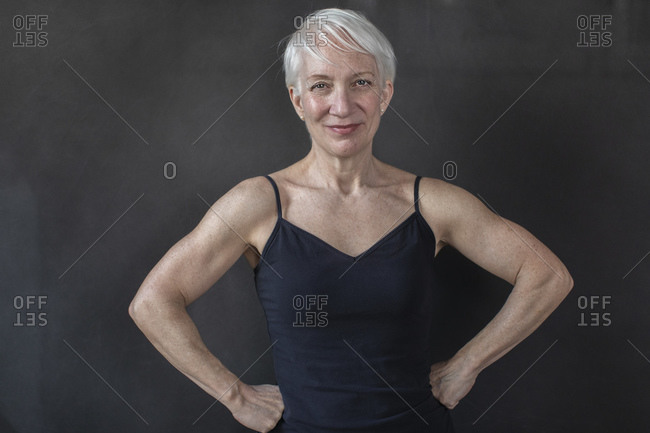 Portrait of confident mature fit woman with hands on hip smiling against black background