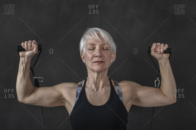 Confident active mature woman exercising with resistance band against black background