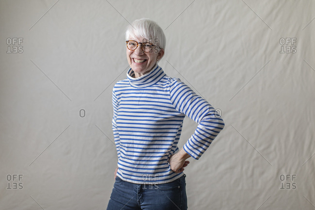 Portrait of cheerful woman in striped turtleneck T-shirt standing with hand on hip against white backdrop