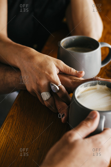 Couple Holding Coffee Cups At Table In Cafeteria