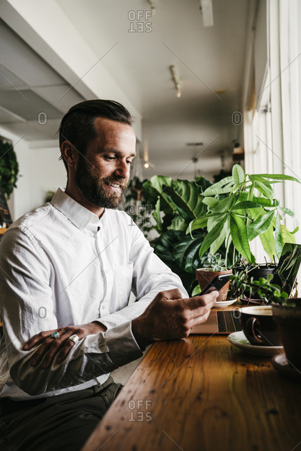 Handsome Bearded Man Surfing On Smartphone At Cafeteria