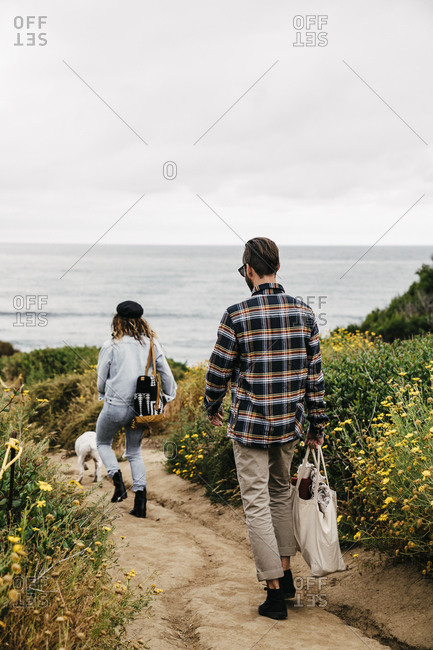 Couple walking to beach with dog