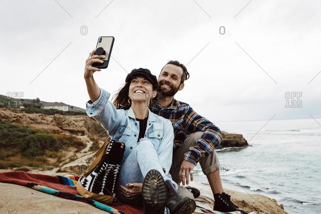 Girlfriend And Boyfriend Taking Selfie On Smartphone at beach