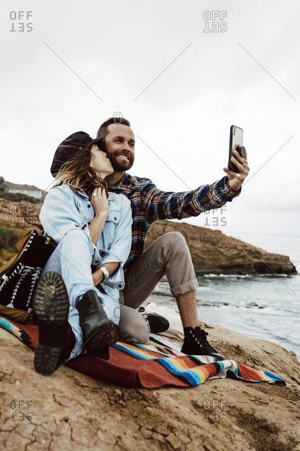 Woman Kissing Boyfriend While Taking Selfie By Sea