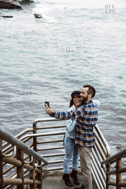 Couple Taking Selfie On Smartphone While Standing On Cliff