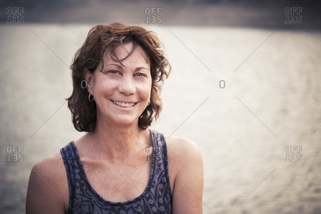 Portrait of happy mature woman standing against lake during weekend
