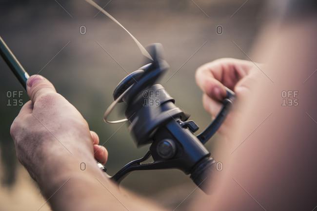 Closeup of cropped man adjusting fishing rod against lake during weekend