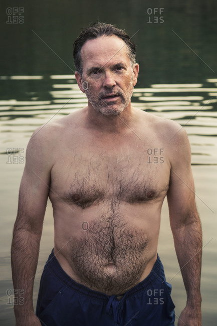 High angle portrait of shirtless mature man standing amidst lake during sunset