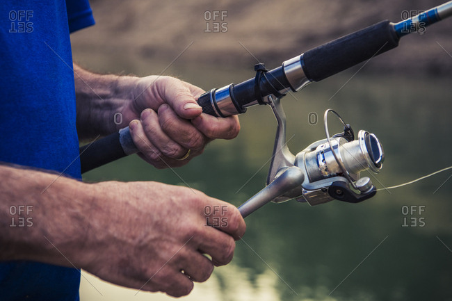 Midsection of young man adjusting fishing rod against lake