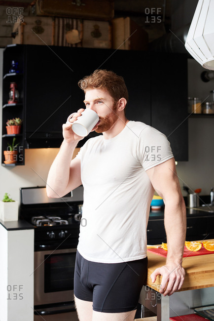 Man Drinking Coffee In Kitchen At Home