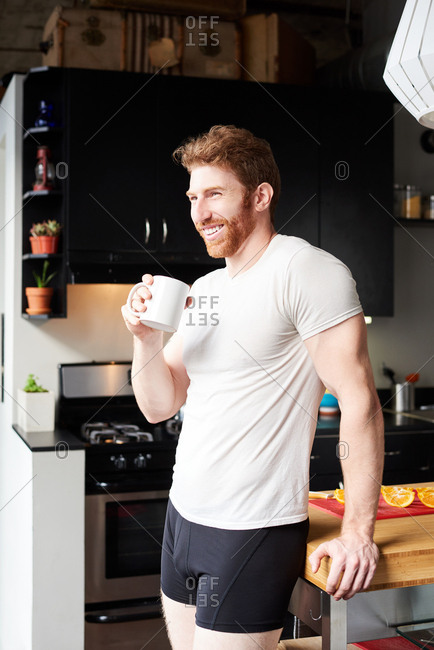 Man Having Coffee While Standing At Kitchen