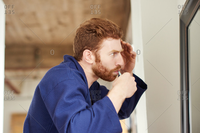 Man In Bathrobe Trimming His Beard While Looking In Mirror