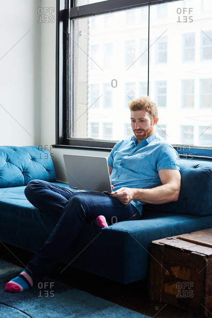 Male Using Laptop On Sofa At Home